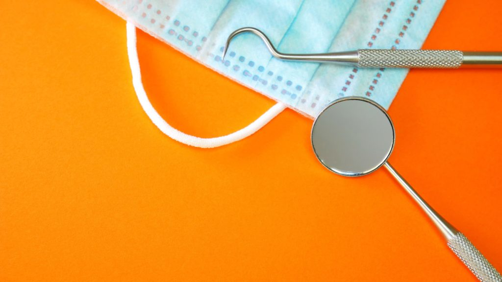 Dental tools and a mask on an orange background