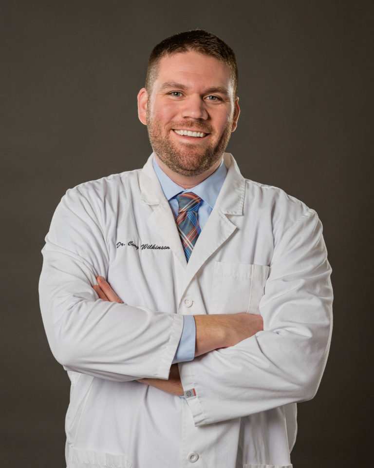 Dr. Cory Wilkinson, dentist at Healthy Smiles Family Dentistry smiling with arms crossed in dental coat