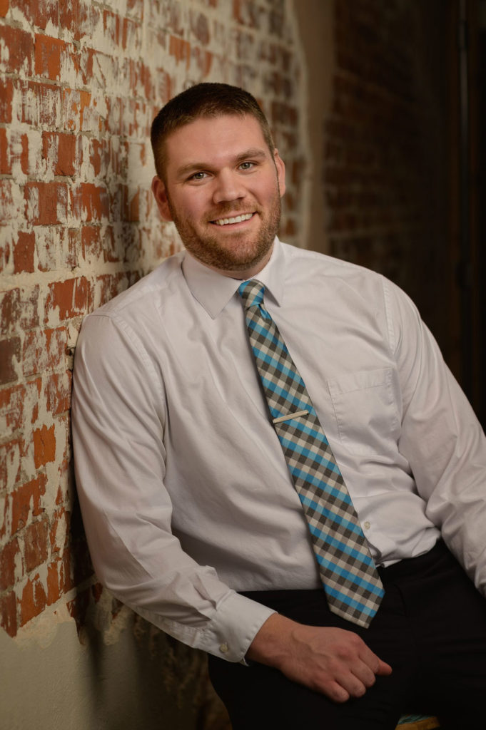 Dr. Cory Wilkinson, dentist at Healthy Smiles Family Dentistry smiling and leaning on brick wall