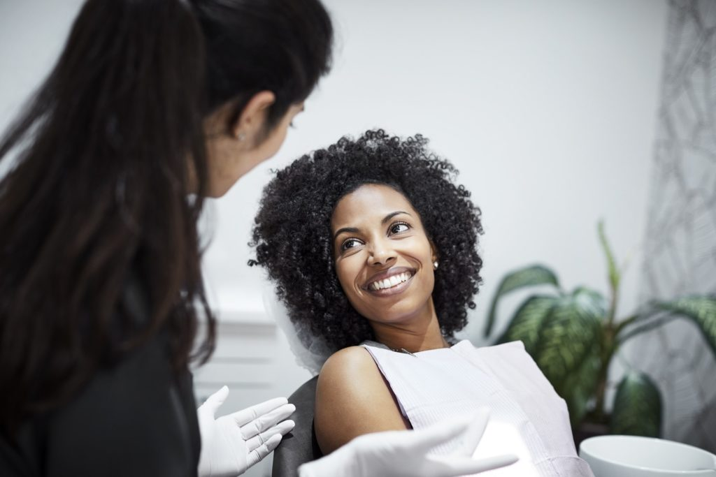 A dental assistant speaking to a female patient who is sitting in an exam chair and smiling