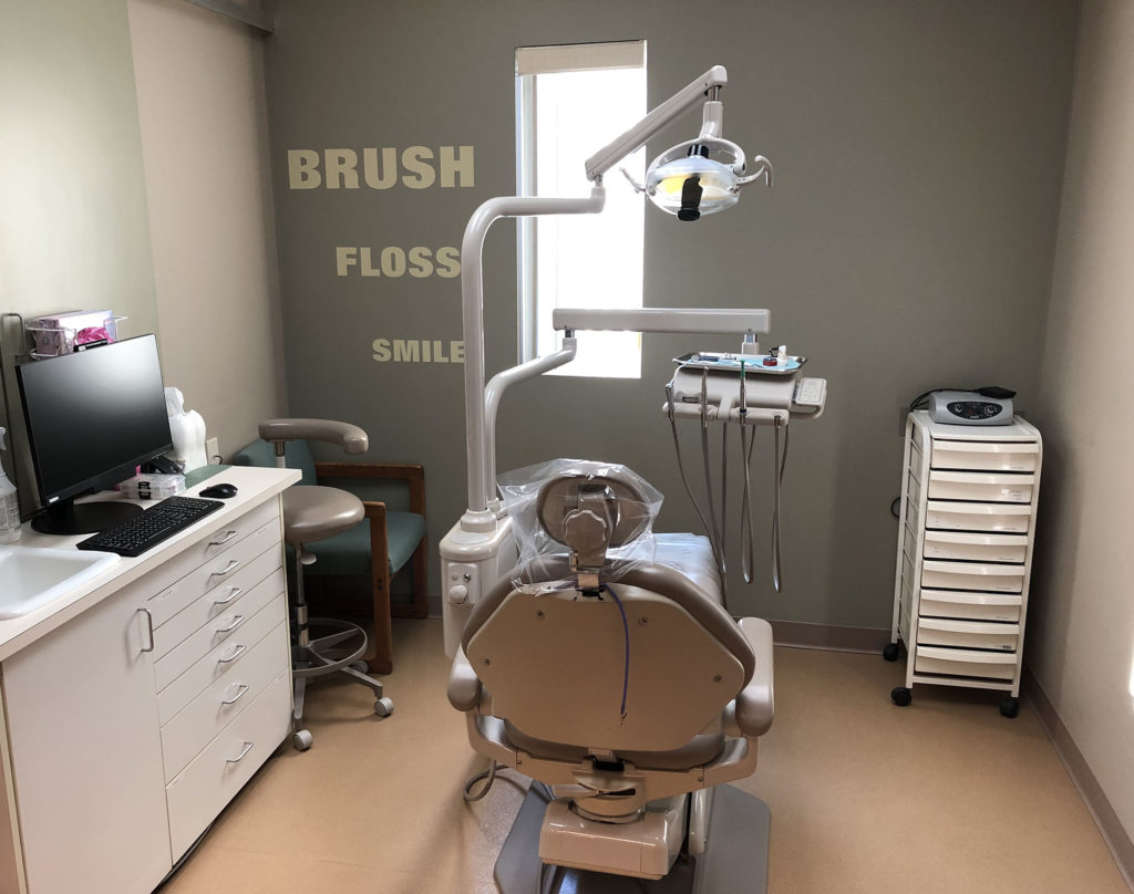 An exam room with a dental exam chair in the middle