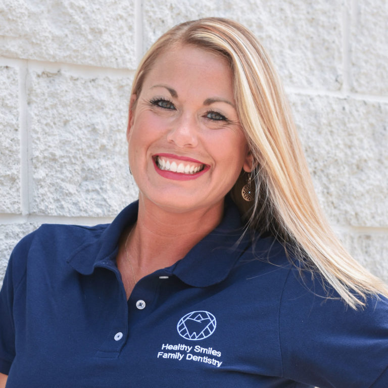 Amy, Dental Assistant at Healthy Smiles Family Dentistry smiling and leaning on grey brick wall
