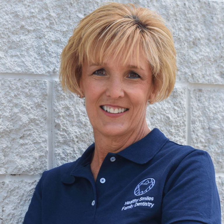 Jill, Dental Hygienist at Healthy Smiles Family Dentistry smiling and leaning on grey brick wall