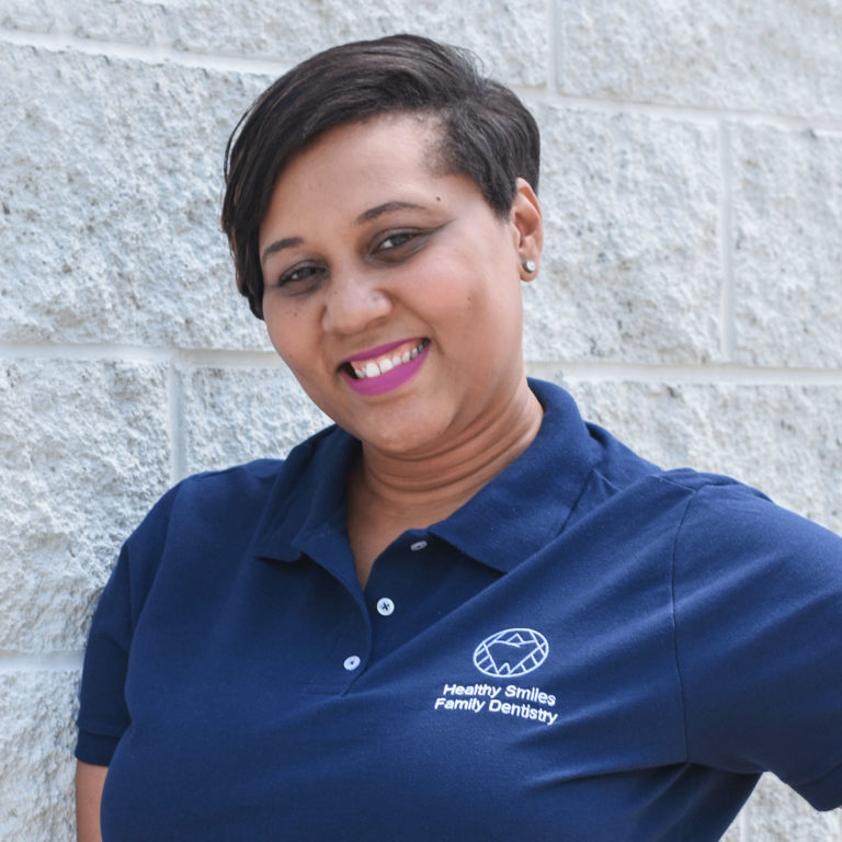 Marquita, Office Manager at Healthy Smiles Family Dentistry smiling and leaning on grey brick wall