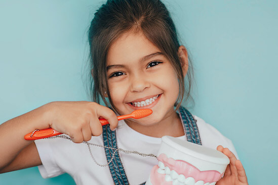child smiling holding a toothbrush near their baby teeth